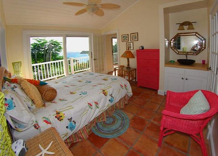 Cottage bedroom with balcony access.