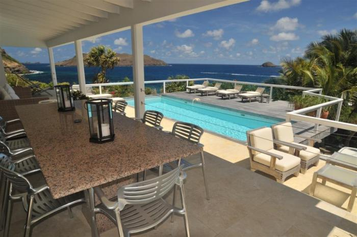 Outdoor dining with pool and ocean views.