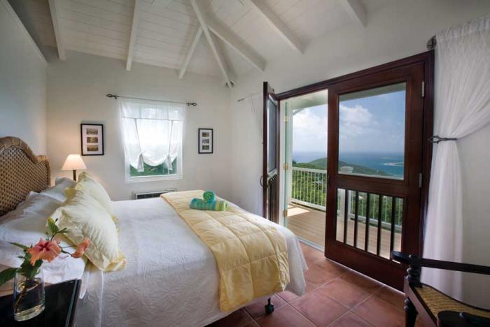 Bedroom with balcony access and views to the sea.