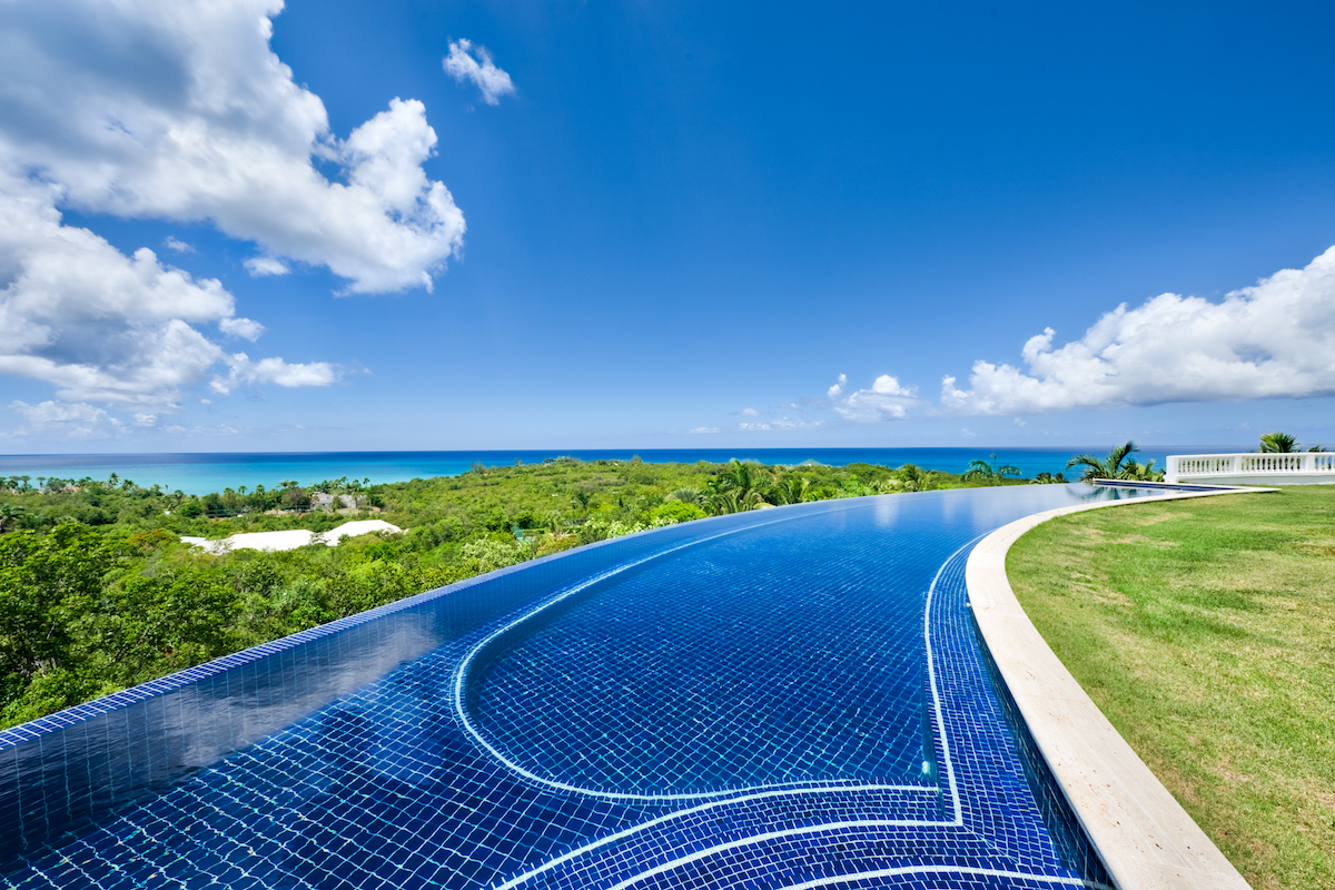 Gorgeous infinity edge pool surrounding the back lawn