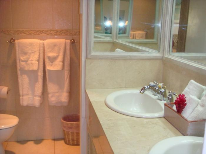 Bathroom with  glass enclosed shower and double sink marfil vanity.
