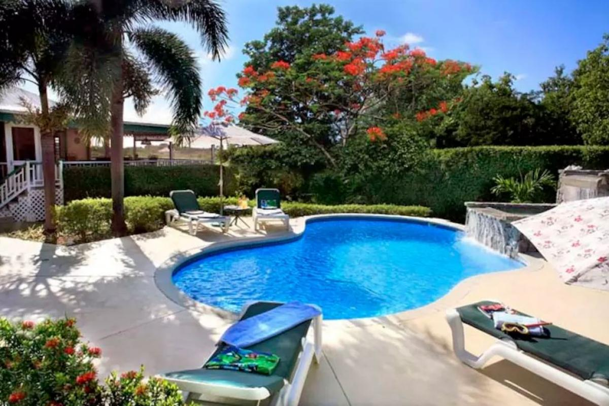 A private pool with a a water feature is the focal point of the back yard