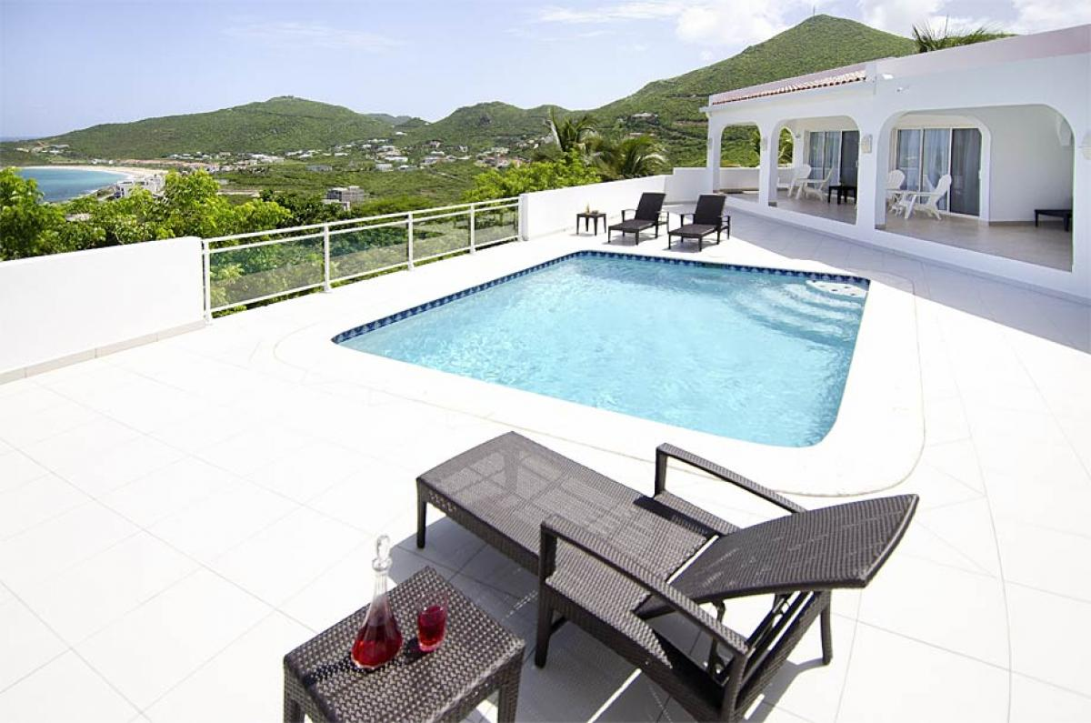 Relax poolside and enjoy views of the Caribbean at Rising Star Villa