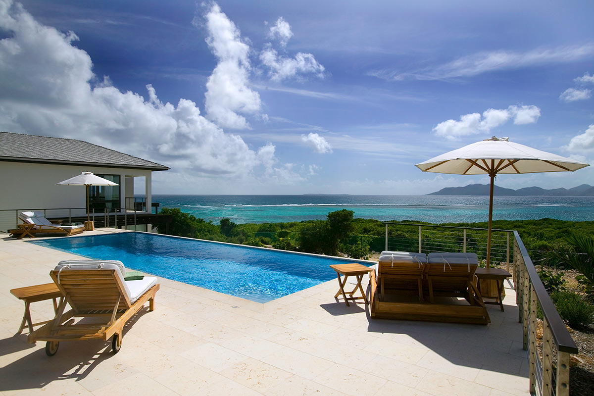 Lounge by the pool at Anani and enjoy views of the Caribbean and the mountains of St. Maarten beyond