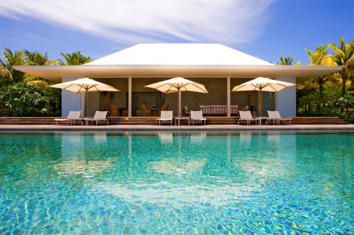 Umbrellas shade the poolside lounge seating.