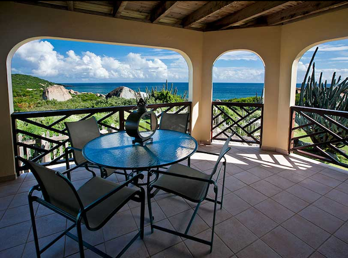Patio dining with ocean and hillside views.