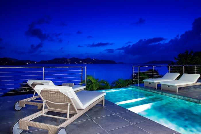 The pool lit up at night, overlooking the ocean.