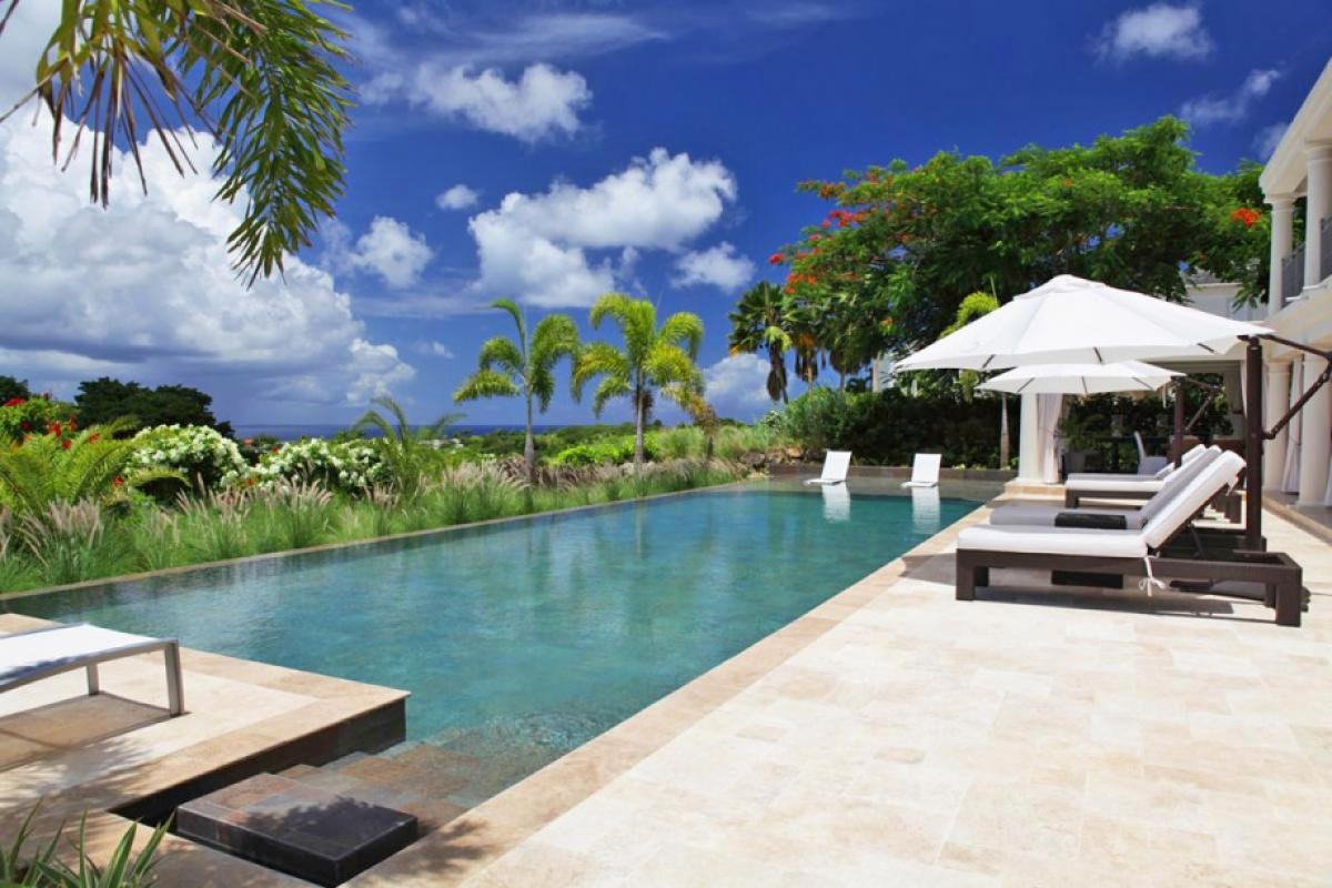 Lelant's elegant pool deck surrounded by lush tropical greenery