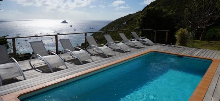 Swimming pool is surrounded by chaise lounge chairs.