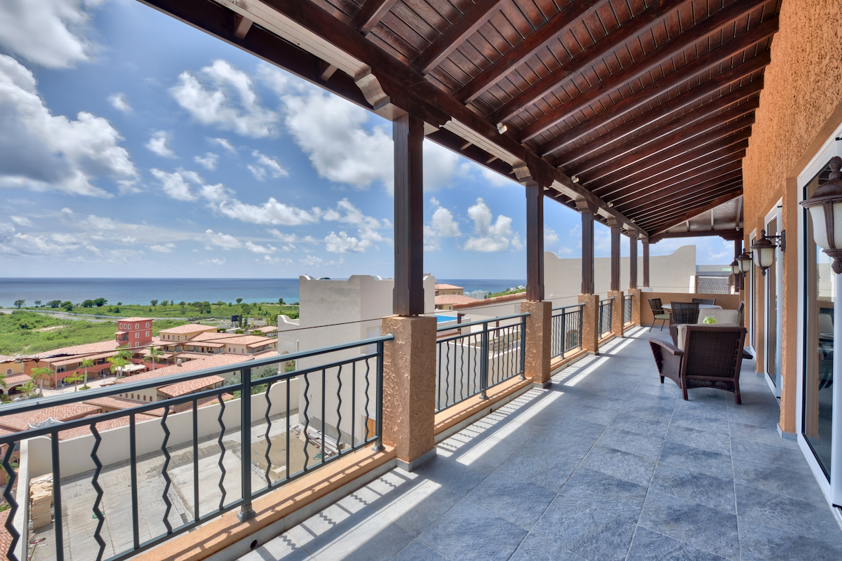 Balcony patio with views of the ocean in the distance